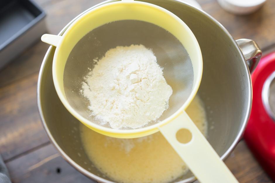 Сито с мукой над чашей со смесью из сахара и яиц